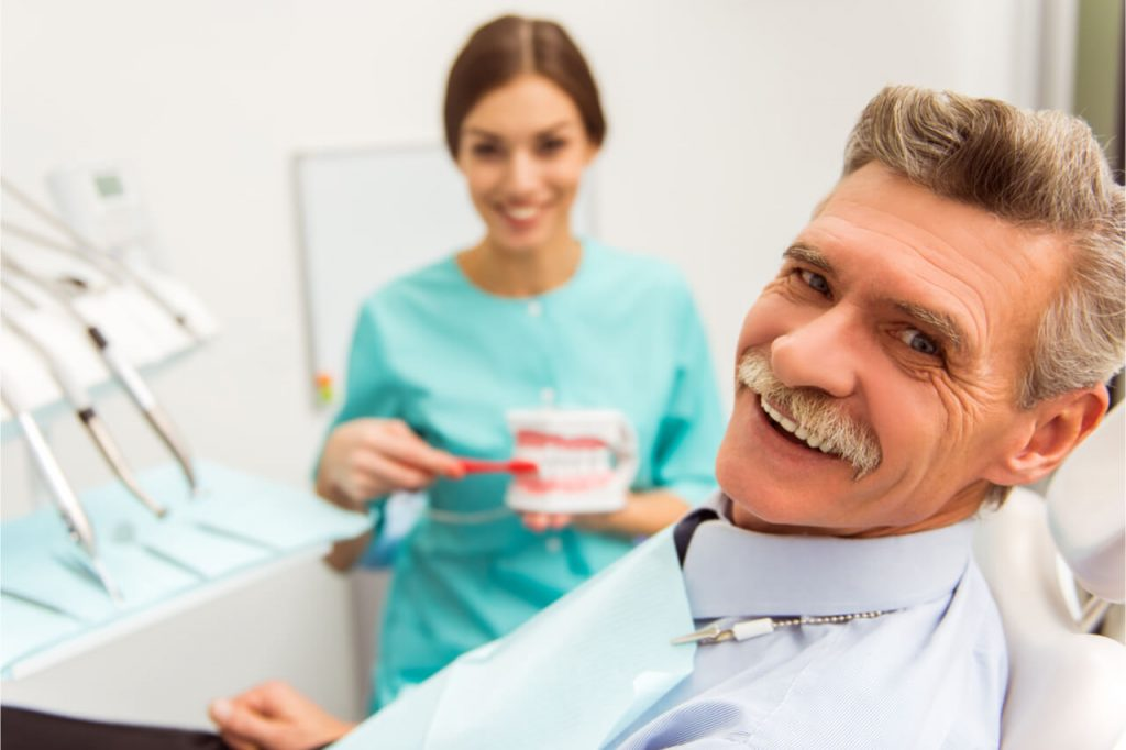 The dentist is relining the patient's denture.